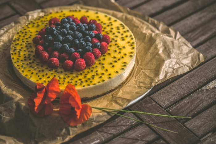 Cake photography of a fruity cheese cake on a rustic table