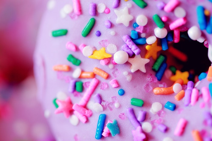 Creative food photography close up of a pink frosted donut with sprinkles