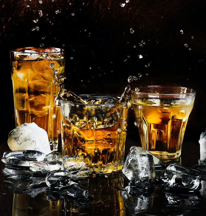 Three whiskey cocktails surrounded by ice