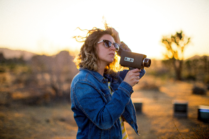 A woman in sunglasses holding a camcorder