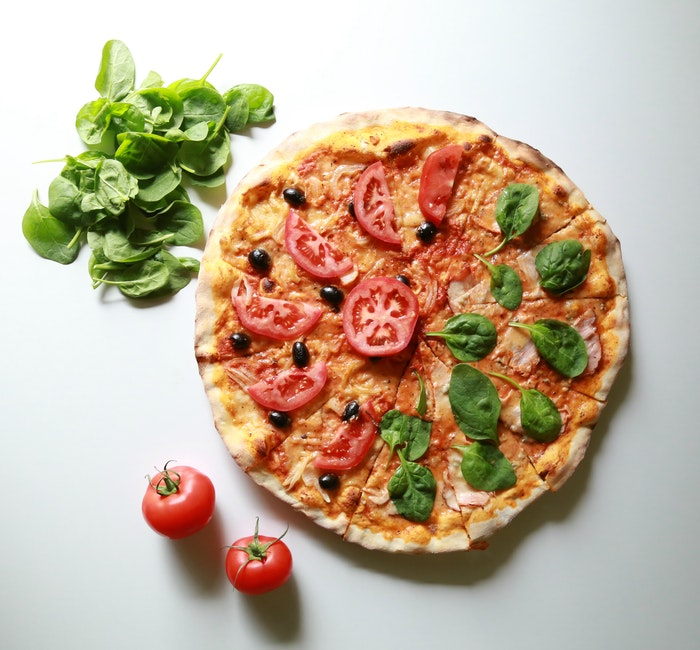 Flat lay food photo of a pizza plus extra ingredients