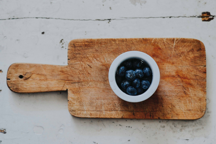 Un tazón de arándanos sobre una tabla de cortar de madera