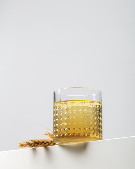 Un vaso lleno de bebida alcohólica dorada con un fondo blanco.