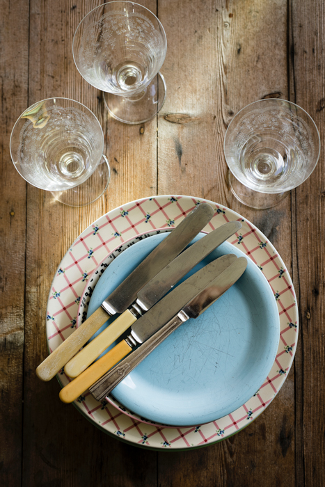 Knives placed on top of plates on a wooden table