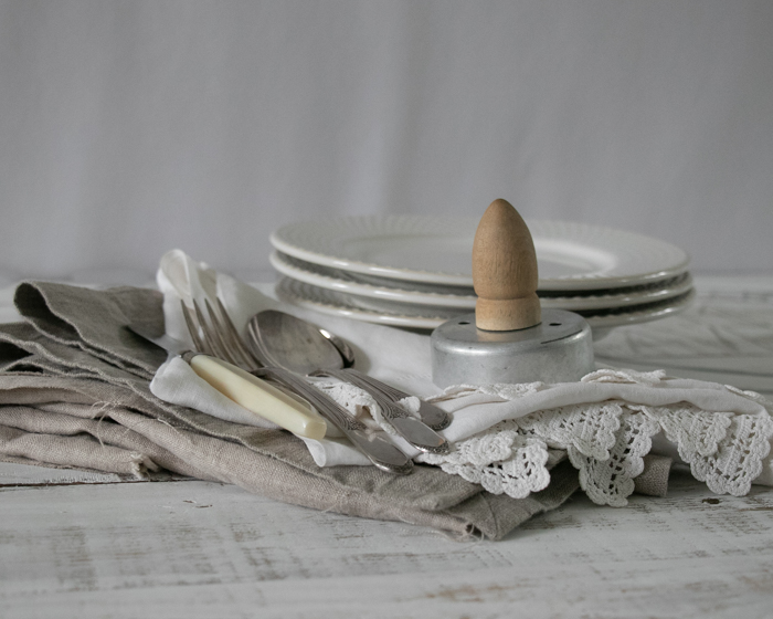 Photo of silverware, plates and different linens on a table
