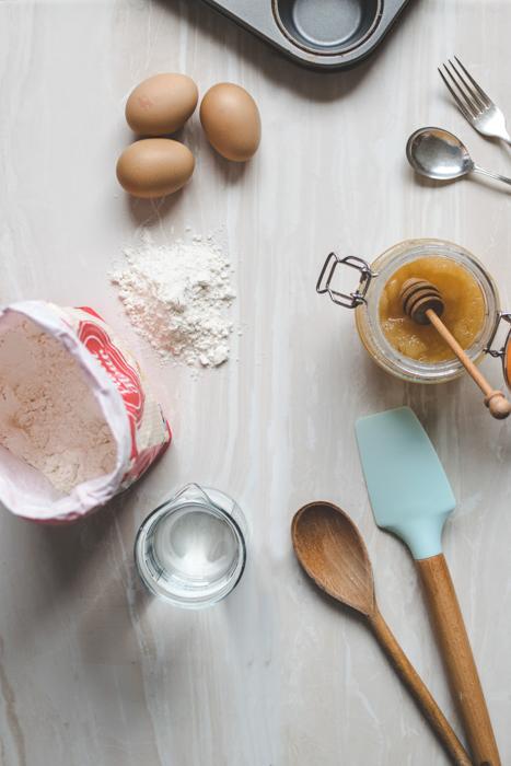 Utensilios de cocina, harina y huevos sobre una superficie de mármol