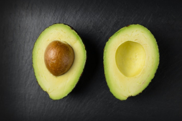 Flatlay food photo of an avocado cut in half