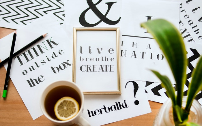 Flat lay of different typography, a teacup, plant and stationary
