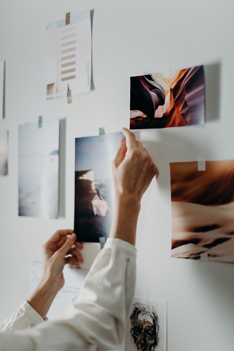 Uma pessoa pendurando impressões fotográficas em uma parede