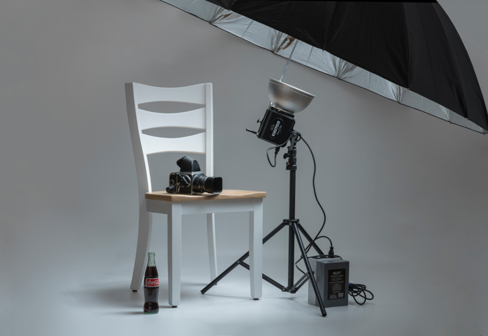 Photo of a studio setup with a chair, camera, and flash