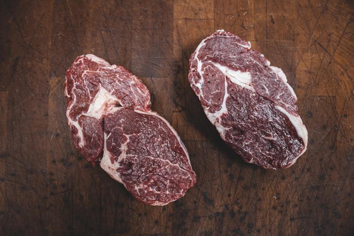 Tiro de dois cortes de carne crua em uma placa de madeira