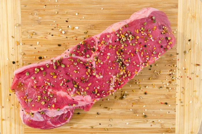 Postura plana de um corte temperado de carne crua em uma placa de madeira