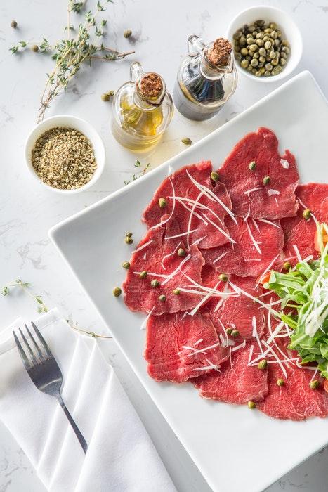 Visão aérea de carne em fatias finas e condimentos