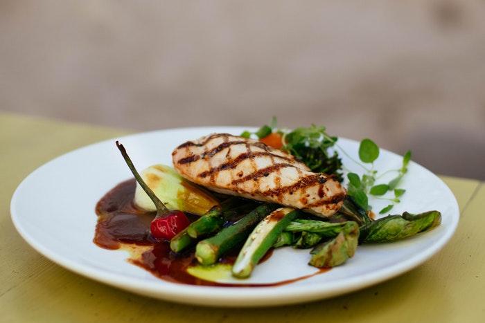 Um prato de peito de frango servido com legumes.