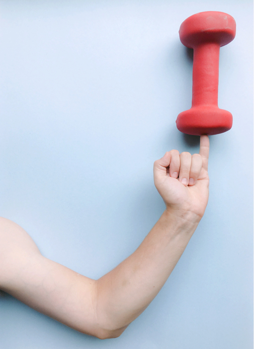 An image of a perspective trick with an arm holding a weight on the pinky finger.