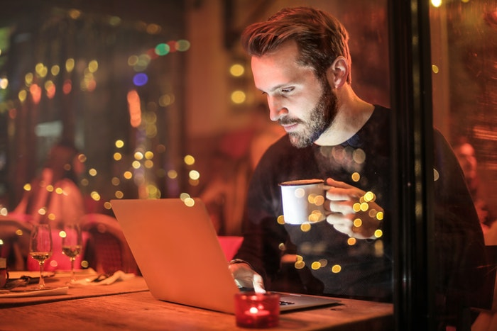 Candid shot of a man in a cafe at night illuminated by neon lights