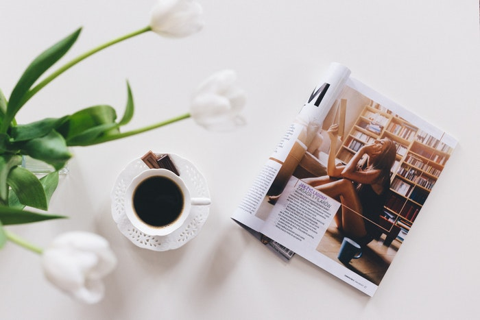 A magazine one a table with a cup of coffee and flowers