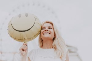 Woman smiling and holding a smiley face baloon