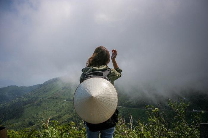 Uma garota fica na frente de uma paisagem montanhosa