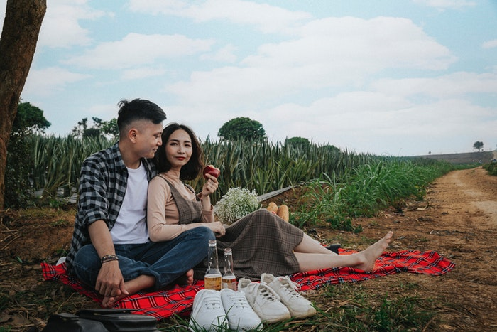 A couple having a picnic photoshoot under a tree
