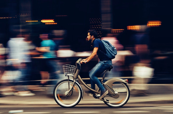 A man riding a bike past a busy marketplace