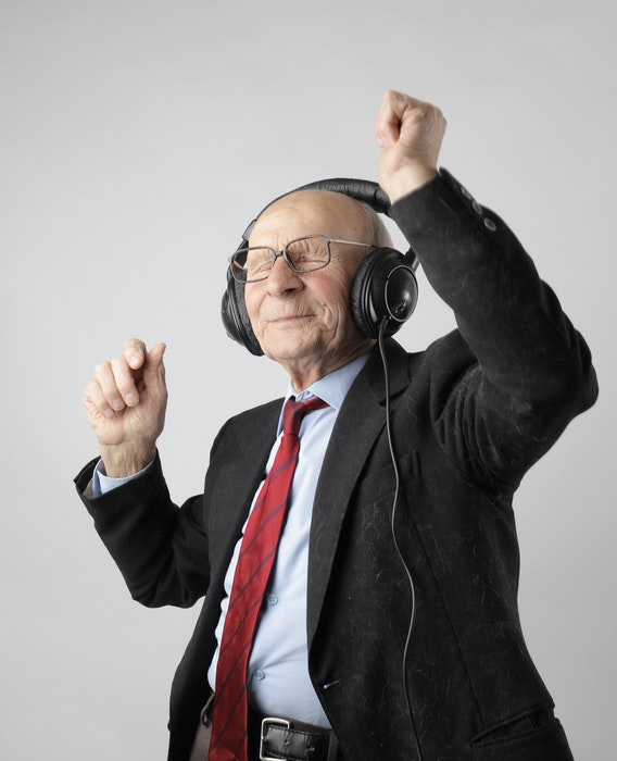 An old man wearing headphones and dancing