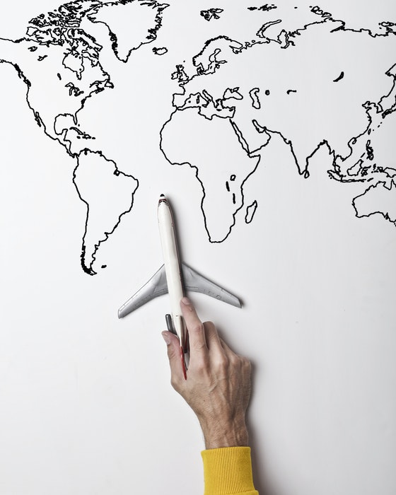 A hand holding a model airplane on a handdrawn map of the world