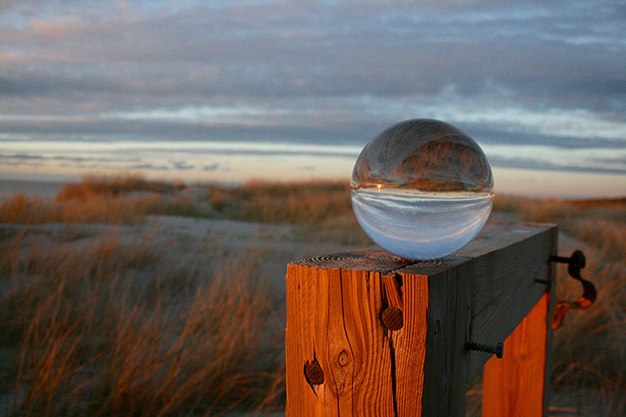 A beautiful landscape at sunset is reflecting in a crystal ball.