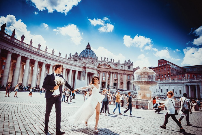 A wedding portrait of the newlyweds walking hand in hand in an outdoor plaza