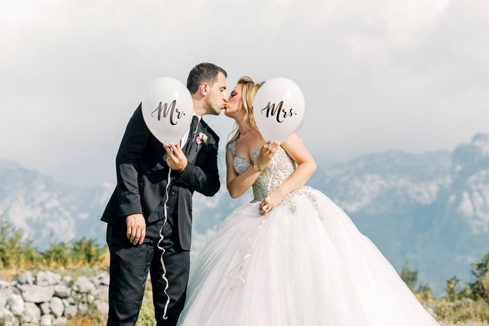 Newlywed couple kissing outdoors and holding 'Mr & Mrs' Balloons