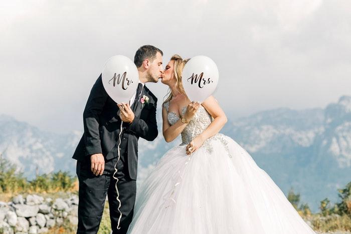 Casal recém-casado se beijando ao ar livre e segurando balões do tipo