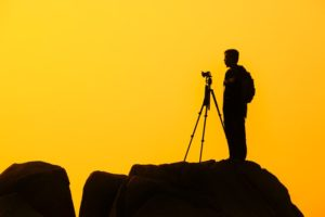 A wildlife photographer silhouetted against the sunset