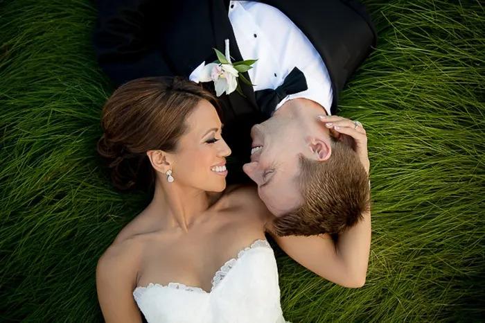 Retrato de casamento do casal recém-casado, deitado na grama