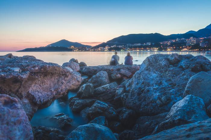 Una escena costera rocosa al atardecer.