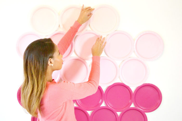 Uma pessoa pendurando pratos rosa como fundo de foto DiY