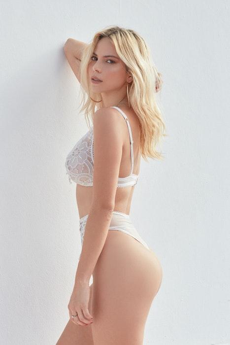 A blonde girl in lingerie posing for boudoir photos