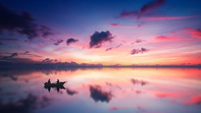 Nuvens coloridas sobre um lago com a silhueta de um barco
