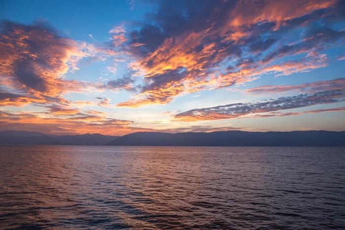 foto de nuvens e pôr do sol sobre uma enorme paisagem aquática
