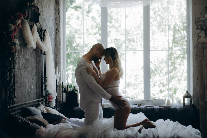 A couple embracing on a cosy bed
