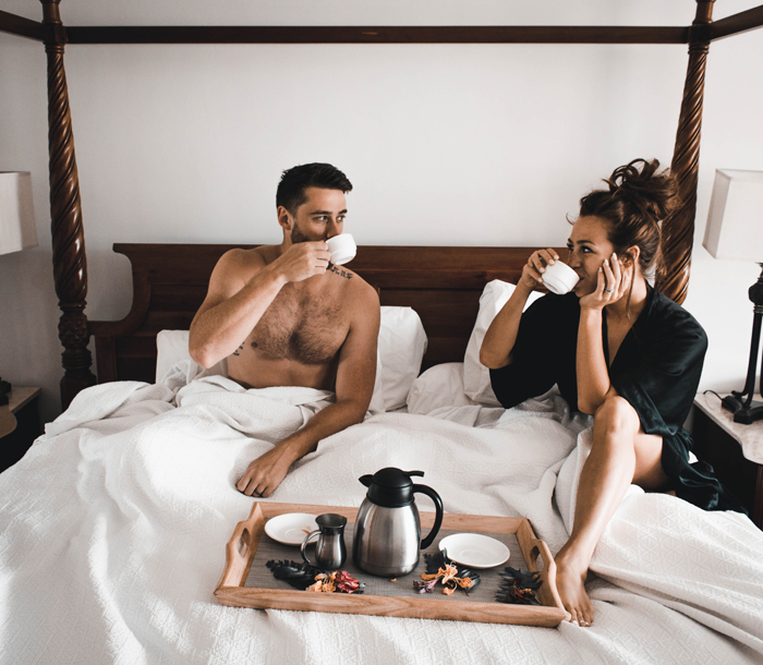 A couple drinking coffee in bed together