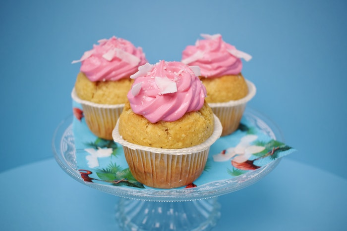 a photo of three cupcakes with pink frosting