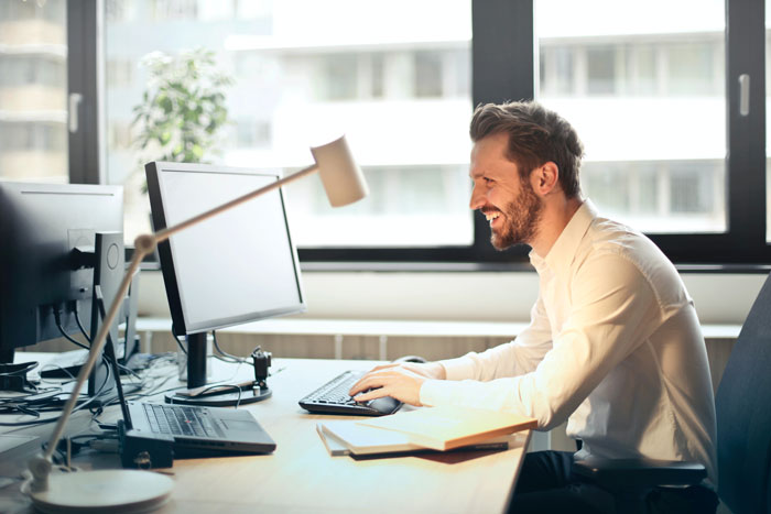 A man at an office desk using email marketing