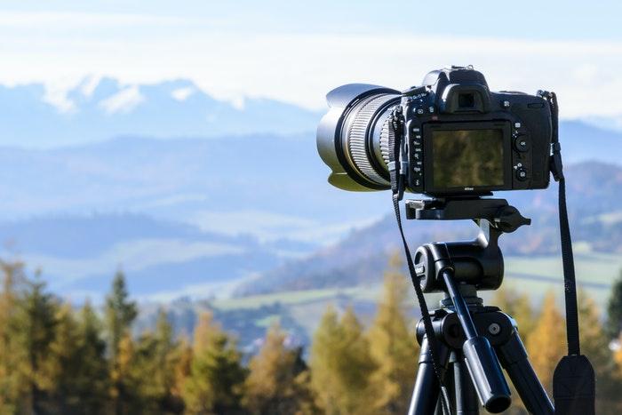 Uma câmera em um tripé com uma paisagem montanhosa