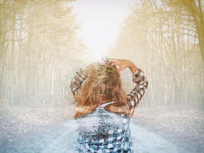 Uma imagem duplamente exposta de uma garota andando pela floresta