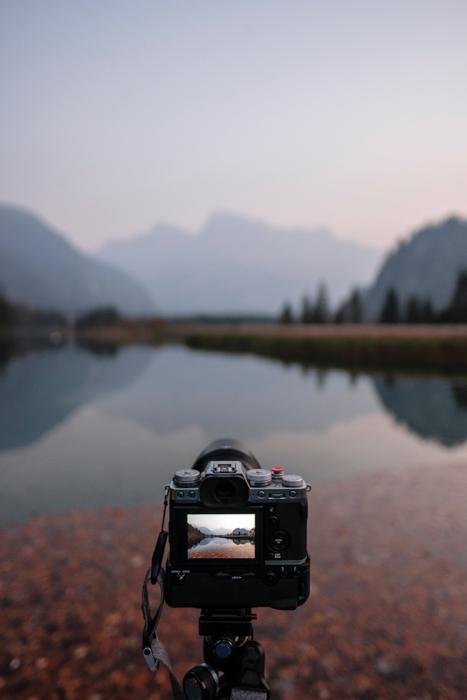 Una cámara DSLR montada sobre un trípode junto a un lago