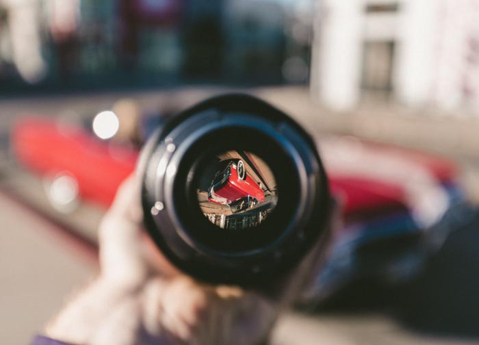 Una persona sosteniendo una lente de cámara frente a un auto rojo.