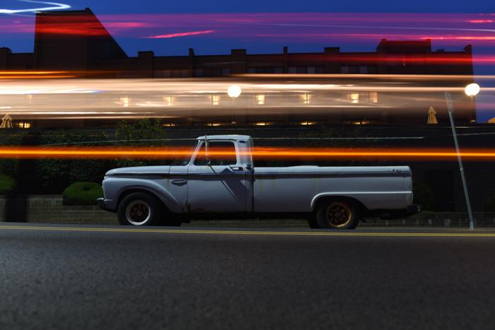 Transmisión de colas de luz por la noche frente a un camión en movimiento