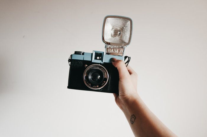 A vintage camera held in the air