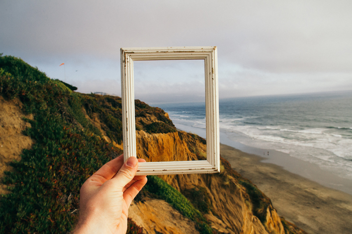 A person holding a picture frame up to a landscape