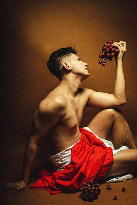Foto de um modelo masculino em estilo grego antigo pose com uma uva